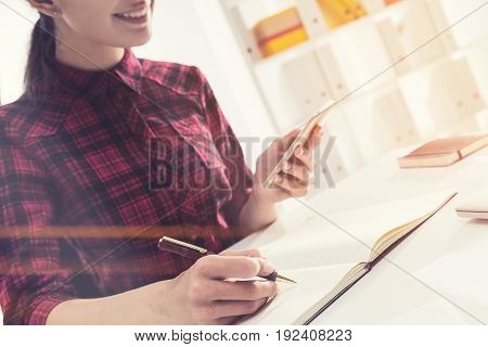 Close up of an unrecognizable young woman in a white office. She is looking at a smartphone screen and writing down the contacts. Toned image.