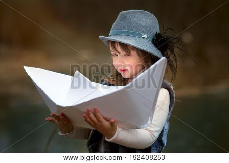 Girl with big paper boat near river at spring cloudy day