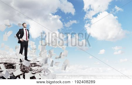 Side view of a confident businessman standing on a rock with his hands on the waist and looking at a city around him. There are papers flying around. Mock up