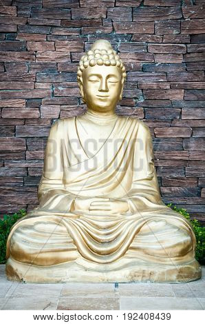 Golden Buddha statue against a brick wall background.