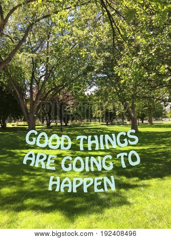 Inspirational quote on scenic park landscape with green grass field and big trees on a sunny day. Good things are going to happen.