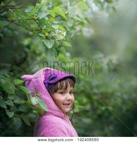 Little girl portrait in a lilac bunches at cloudy day