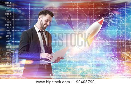 Side view of a young bearded businessman holding a laptop and standing against a futuristic background with graphs and a start up rocket. Mock up toned image double exposure