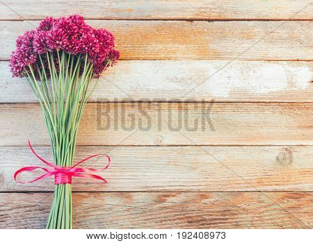 bouquet of beautiful purple allium flowers tied with a purple ribbon on wooden retro background with space for text. Lay Flat top view
