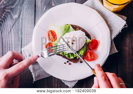 Young Man's hands as he is having breakfast. Rye Bread Toast and Poached Egg with Green Salad Cherry tomato cup of coffee and Orange Juice on the Wooden Table Background. Healthy Breakfast content