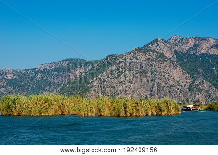 TURKEY, MUGLA , DALYAN. The Dalyan River with tourist boat in the straits of the river