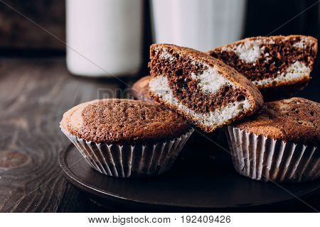 Homemade sweet chocolate vanilla muffins from two types of dough with glass and bottle of milk on wooden table background. Copy space