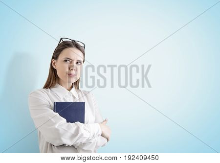 Portrait of an alert young woman with fair hair holding a blue book and standing with crossed arms near a blue wall. Mock up