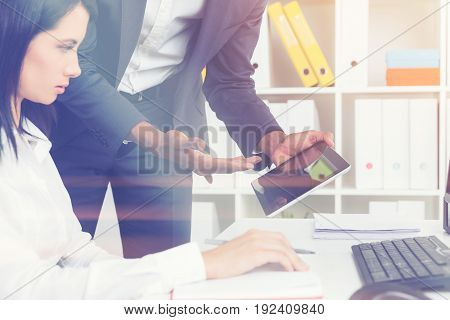 Close up of a businesswoman sitting at her computer in a white office. There is an unrecognizable colleague standing near her with a tablet computer and showing the screen. Toned image