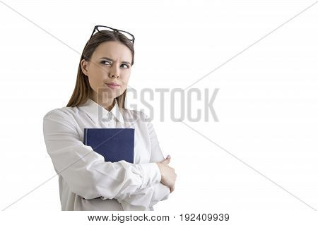 Isolated portrait of an alert young woman with fair hair holding a blue book and standing with crossed arms. Concept of a constant vigilance