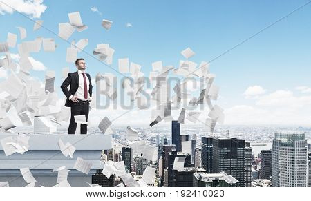 Side view of a confident businessman standing on a skyscraper roof with his hands on the waist and looking at a city around him. There are papers flying around. Mock up