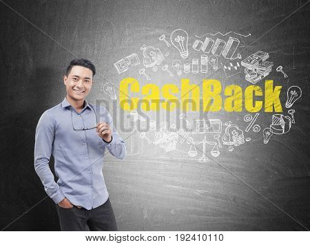 Portrait of a smiling Asian businessman wearing a blue shirt and dark trousers and holding glasses. Blackboard with a large cash back sketch