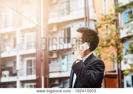 Close-up Smart Business Man Wearing Modern Black Suit And White Shirt And Calling  On Mobile Smart P