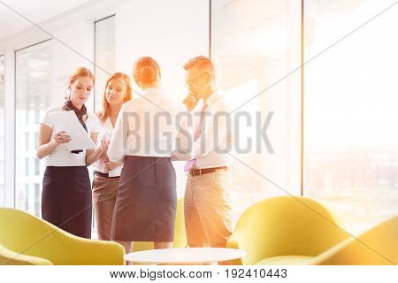 Business people discussing over documents in office lobby