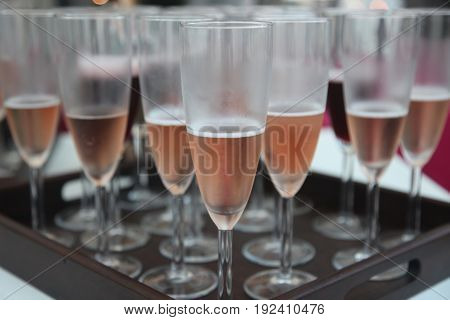 Chilled Rose sparkling wine in champagne flutes served on a brown tray