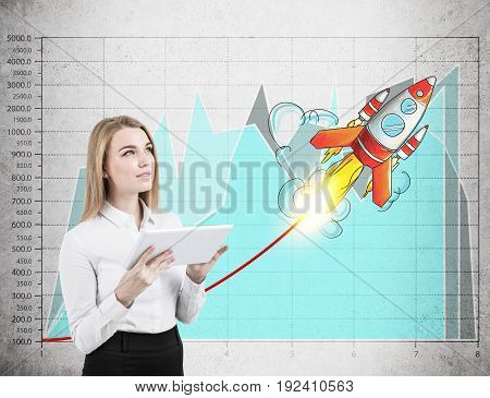 Portrait of a blond woman with a tablet standing against a concrete wall background with graphs on it. Start up rocket