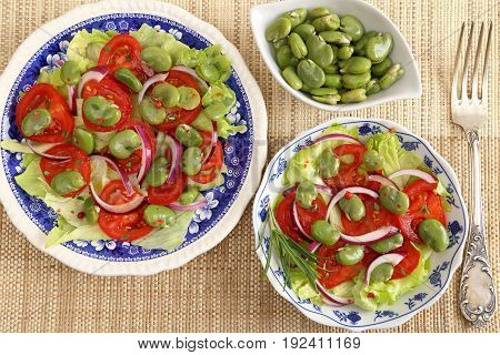 Close up of a broad beans salad with tomato and red onion.