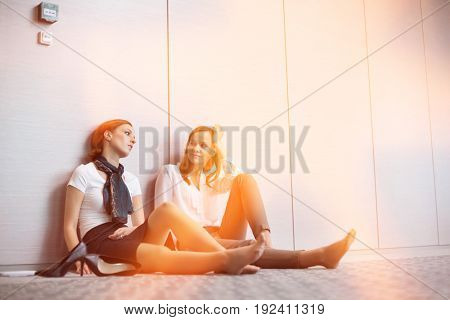 Tired businesswomen sitting on floor in office