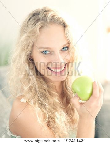 Portrait of happy young woman holding apple in house