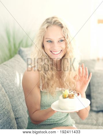 Happy woman gesturing while holding cake in house