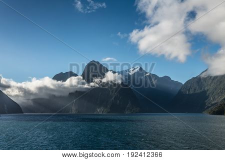 Fiordland National Park New Zealand - March 16 2017: Looking over the blue salt waters into the fjord of Milford Sound. Huge mountains sharp cliffs with low hanging white clouds under blue sky.