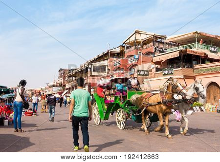 Marrakech Morocco - May 04 2017: Horse-drawn carriage taking tourists for a ride on the Jemaa el-Fnaa square UNESCO World Heritage Site in Marrakech Morocco Africa