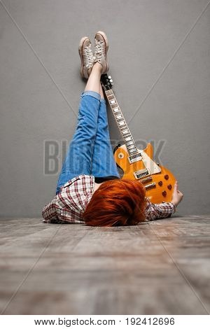 Portrait of young pretty girl with red hair lie on floor with guitar over grey background.