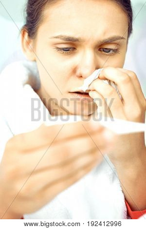 Close-up of worried woman taking her temperature
