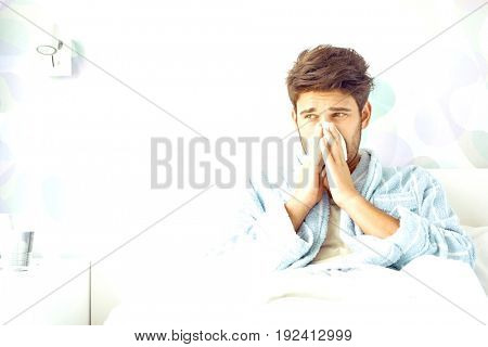 Sick man blowing his nose while sitting on bed at home