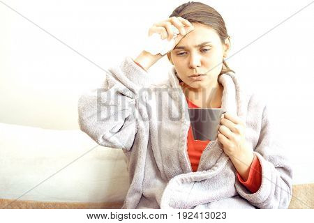 Young woman suffering from cold having coffee on bed