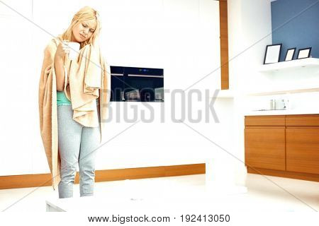 Young woman wrapped in blanket holding coffee mug while suffering from headache in house