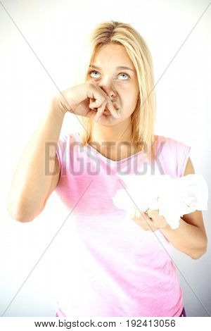 Young woman suffering from cold holding tissue papers against gray background