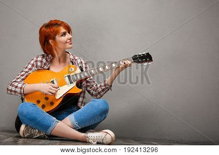 Portrait of young pretty girl with red hair sitting on floor with guitar over grey background. Copy space.