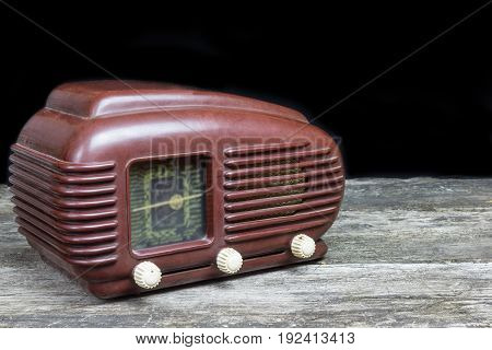 Side view of old radio standing on the old wooden desk. Black background. All potential trademarks are removed and blurred.