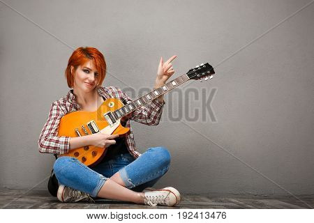 Portrait of young pretty girl with red hair sitting on floor, looking at camera with guitar over grey background. Copy space.