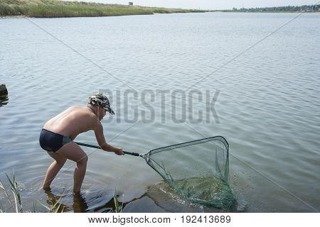 In the summer in the afternoon the boy is fishing in the lake with a net.