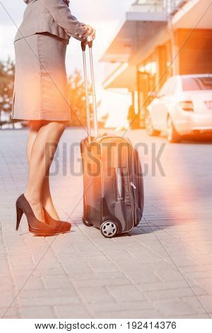 Low section of businesswoman standing with suitcase on driveway
