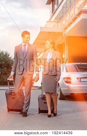 Full-length of business couple with luggage walking outside hotel