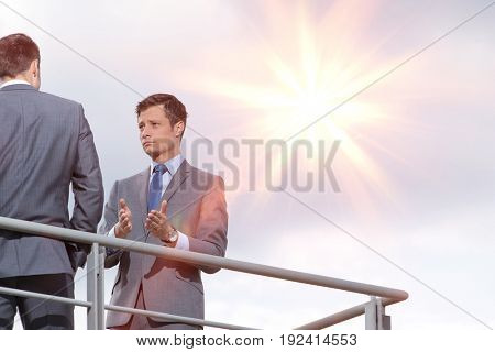 Businessman gesturing while communicating with coworker against sky