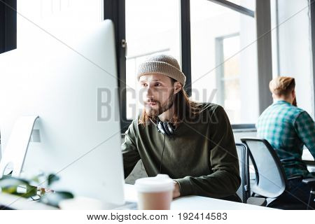 Image of young handsome man work in office using computer. Looking aside.