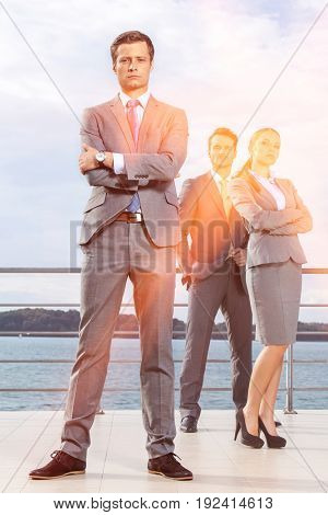 Portrait of confident young businessman standing with coworkers on terrace against sky