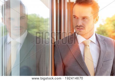 Businessman looking away while leaning on glass door