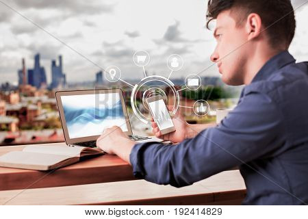 Side view of young businessman using smartphone and laptop placed on wooden windowsill with open book. Blurry city background. Technology concept