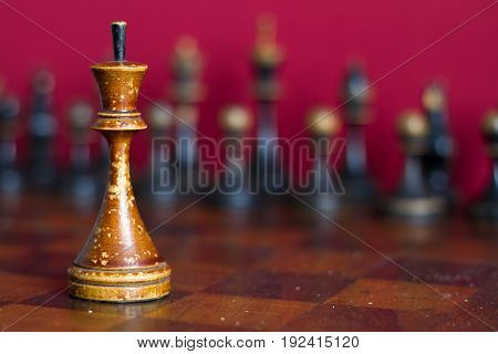 Ancient wooden chess pieces on an old chessboard. On a red background.