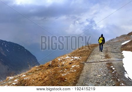 hiker on a mountain path by bad weather