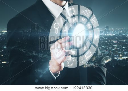Businessman pointing at circular digital business diagram on nigth city background. HUD concept. Double exposure