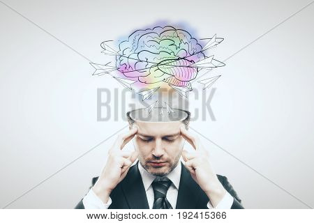 Pensive businessman with abstract brain sketch on light background. Creative thinking concept