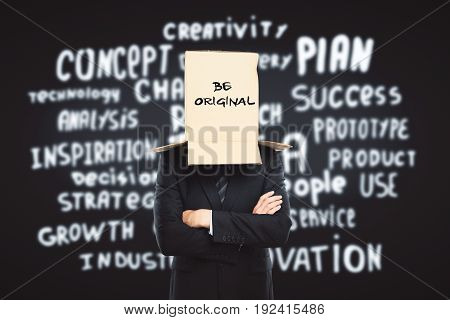 Businessman with cardboard box on head. Dark backgroud with inspirational text. Creativity concept