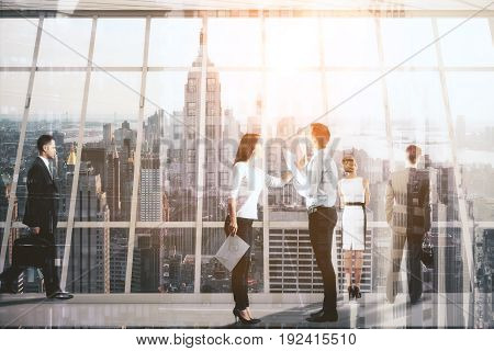 Businesspeople dealing with paperwork in modern concrete interior with New York city view. Team work concept. Double exposure
