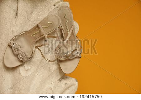 Detail of a pair of wedding shoes creatively displayed against an orange wall.